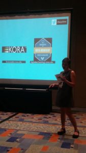 Jolene Smith presenting in front of a screen showing the KORA and MSUDAI logos